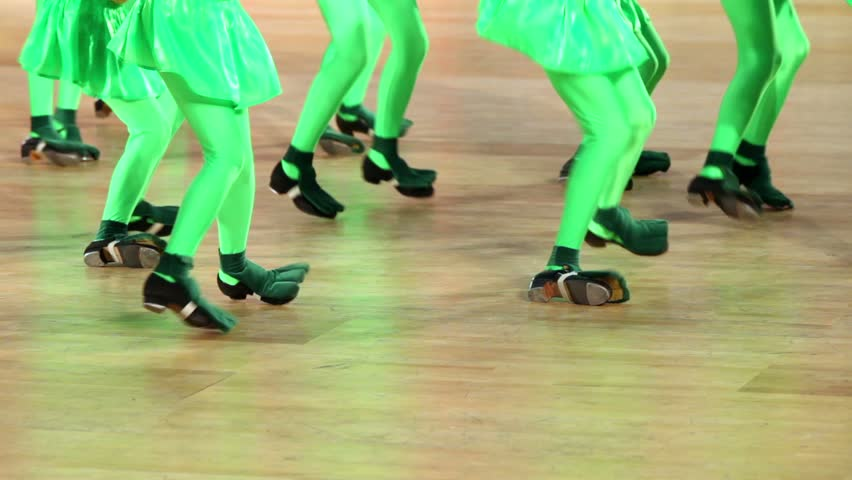 Several girls in shoes with taps and green costume of frog tap dance, only legs are visible