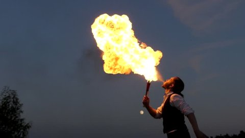 Circus Performer Emits Fire Out of His Mouth. the Action in Slow Motion.