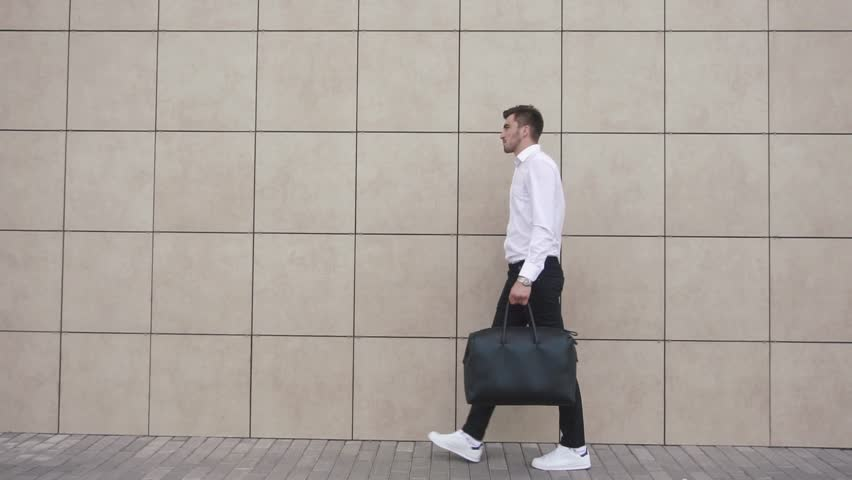 Young confident businessman walking on the background of the office. The modern businessman concept. #18182239
