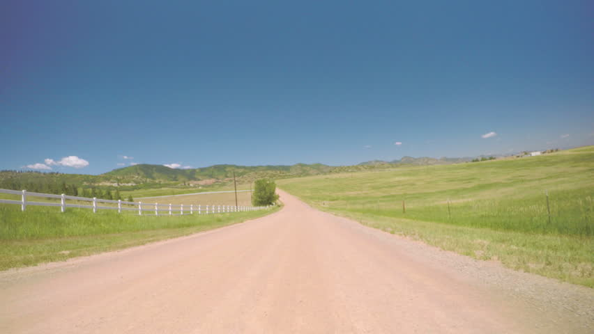 Car driving on rural dirt road in South Denver, near Chatfield State Park.-POV point of view.