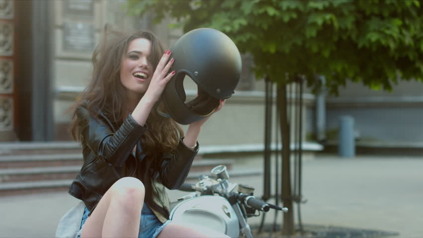 MED Urban portrait of a beautiful Caucasian girl on a motorcycle. Gorgeous brunette female in leather jacket, taking off motorcycle helmet, then laughs. 60 FPS 4K UHD