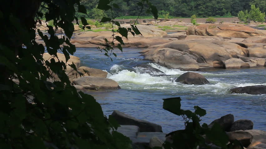 Beautiful rocky river vista through trees from river bank - HD dslr