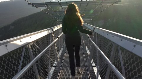 Happily girl run away at narrow pedestrian suspended Skybridge at sunset. Long flowing hair, young woman quickly scamper forward and stop at observation deck above deep ravine at mountain area