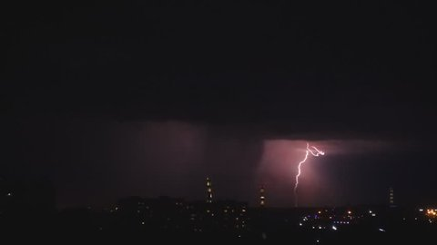 Thunderstorm flashes and lightning over the city, slow motion