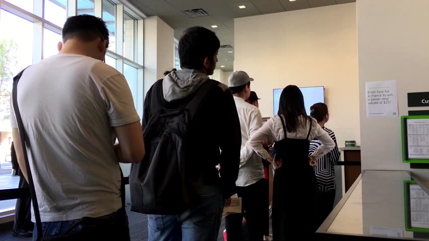 Two business man exchanging business cards and talking stock burnaby bc canada july 22 2016 people line up for waiting reheart Image collections