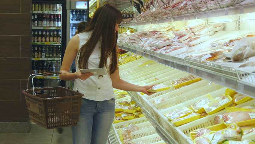 KHARKIV, UKRAINE - JULY 1, 2016: Woman with shopping cart buying refrigerated groceries at supermarket and using tablet pc to check shopping list.