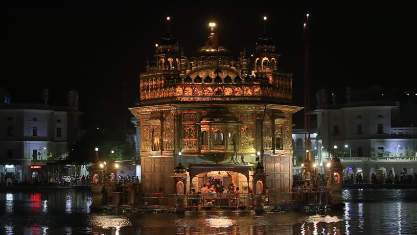 AMRITSAR, INDIA - SEPTEMBER 28, 2014: Unidentified sikhs and indian people visiting the Golden Temple in Amritsar at night. Sikh pilgrims travel from all over India to pray at this holy site
