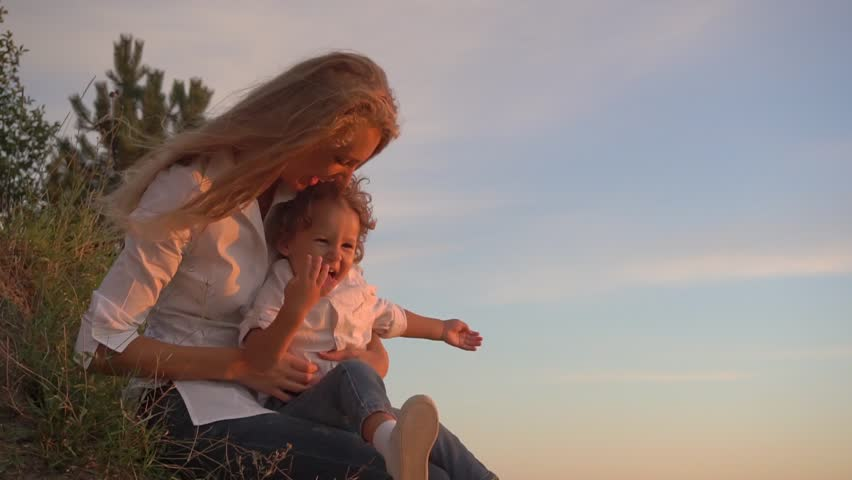 Sweet active little boy laughing sitting on mother's lap at sunset | Shutterstock HD Video #18239419