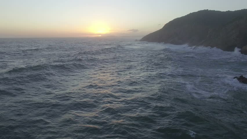 Aerial Shot Flying Low Over Rough Waves at Sunset at Knysna Heads