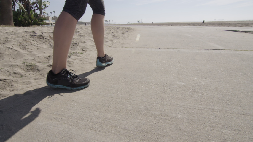 A woman runner going for a run on the beach. - Slow Motion - Model Released - filmed in 4K - filmed at 96 fps - Clip is HD 1920 x 1080 #18272719