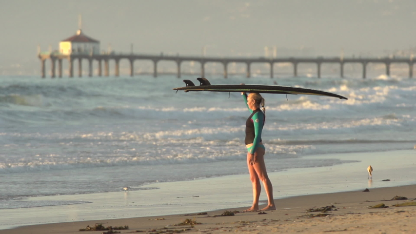 Portrait of a woman stand-up paddleboard surfing at the beach with the Manhattan Beach, CA pier in the background. - Super Slow Motion - Model Released - filmed at 240 fps - Clip is HD 1920 x 1080