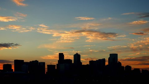 Denver Skyline Silhouette Time Lapse with glowing clouds at sunrise. 4K UHD.
