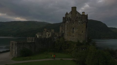 Aerial dusk view Eilean Donan castle people hiking Loch Duich