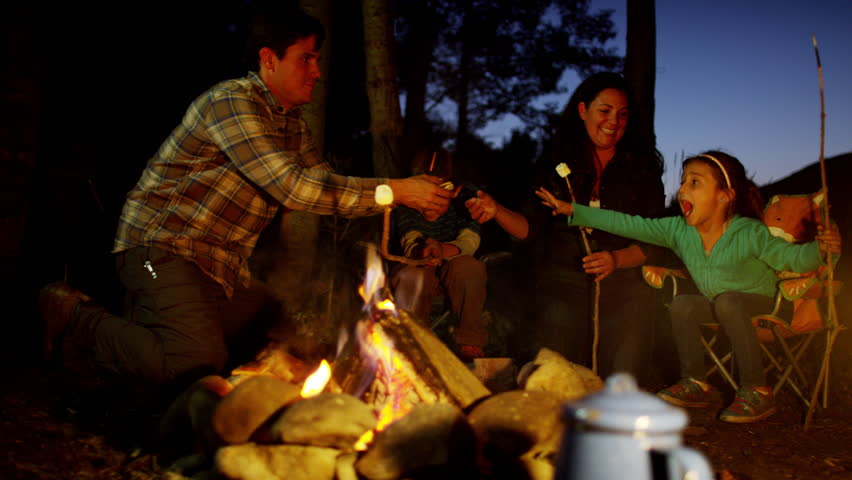 Happy American Caucasian parent and children enjoying toasting smores outdoors