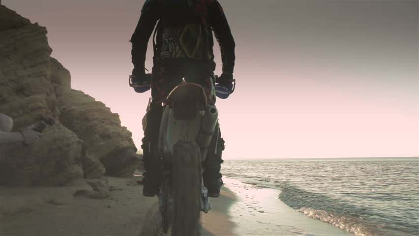 Off-road motorbike rides on a sandy beach in the early morning
