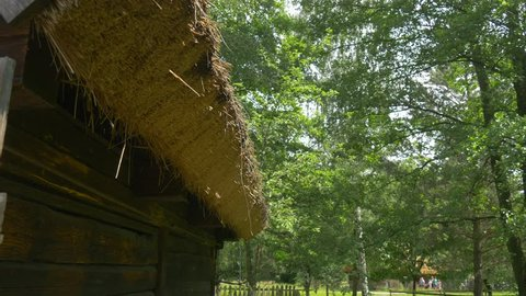 a Fragment of an Old House With Thatched Exterior.old Roof Made From Straw.fresh Green Grass Around Rural Huts