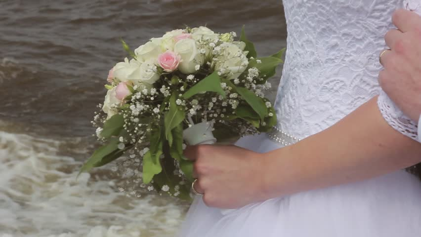 The groom embraces the bride stroking the arm near the sea. Wedding day | Shutterstock HD Video #18322072