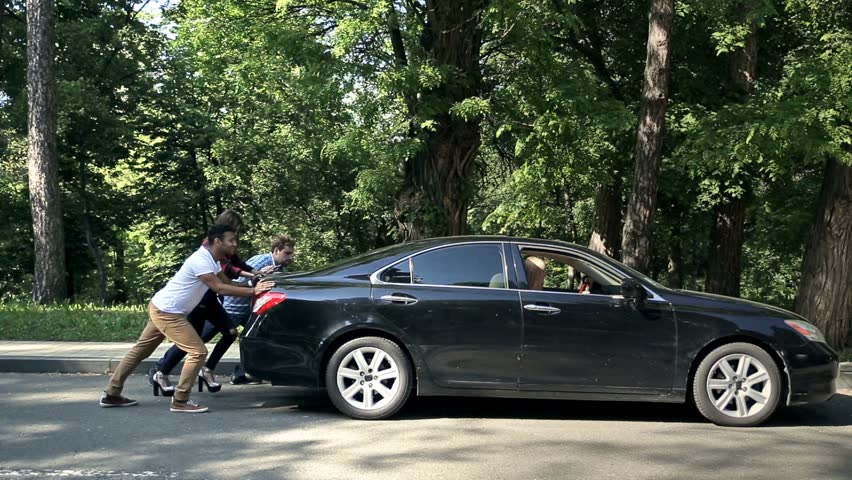 Men helping charming women to push car on road