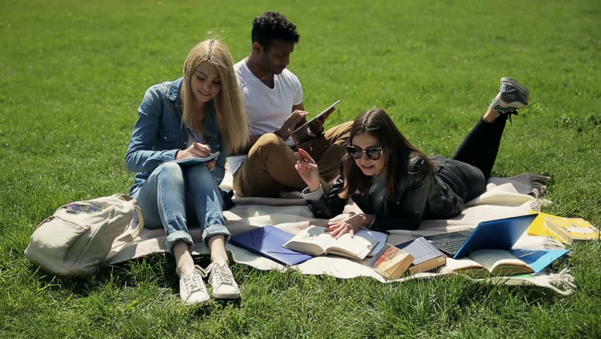 Threesome students studying on campus lawn.