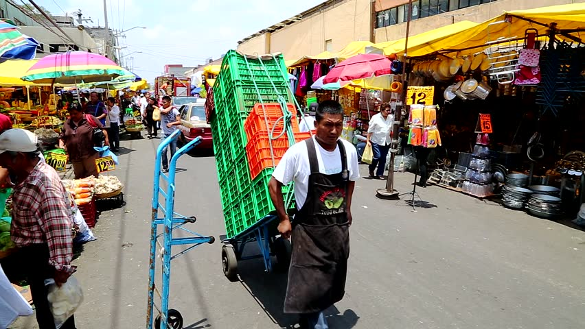Mexico City, Mexico, July 18. Generic image of  busy Food Market. Workers and customers and fresh produce. Fruits, vegetables, chili's, herbs, spices, meat, cheese, plus clothes and art work.