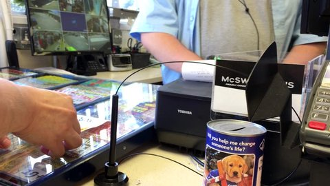 Coquitlam, BC, Canada - July 26, 2016 : Clerk giving customer reciept for buying lottery ticket inside Husky gas station convenient store