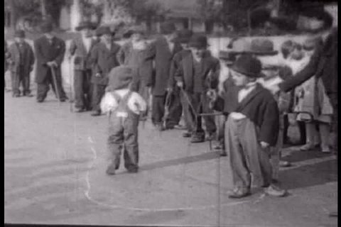 Small children parade in a circle wearing Charlie Chaplin outfits outside on the street in 1927, Martinez, California, (1920s)