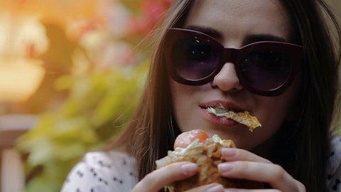 Beautiful Girl Eats Burger on the Street in Chicago. Tasty Burger . Beautiful Girl Savors Burger