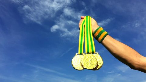 Hand of Brazilian athlete wearing Brazil colors sweatband holding gold medals shining against blue sky in Rio de Janeiro