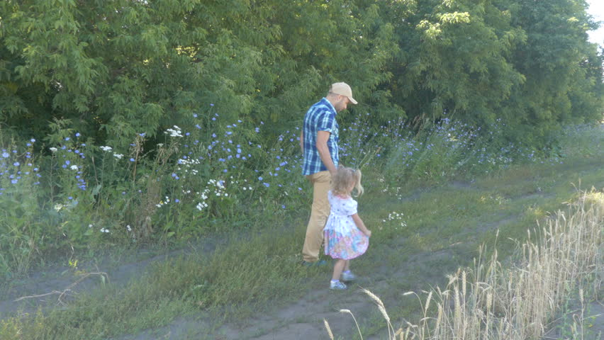 Dad Father and daughter walking outdoors on a forest path hand in hand. Family life. Healthy lifestyle. | Shutterstock HD Video #18376669