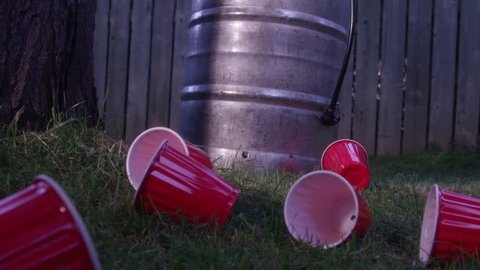 Dolly backwards to reveal mess after a keg party - beer and cups