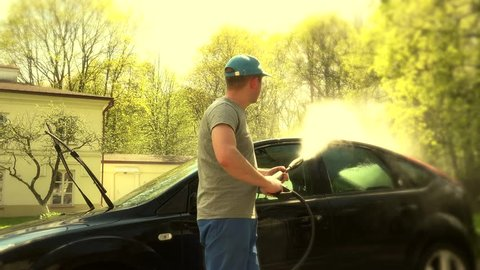 Man washing the windscreen of his car in a cubicle with high pressure water jet