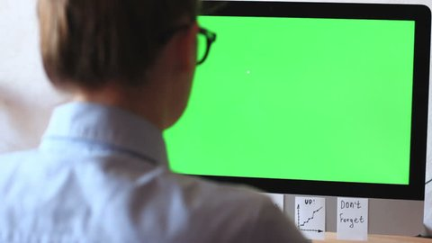 A freelancer working on a computer plastered with notes, reminders, stickers. On the monitor green screen, chroma key.