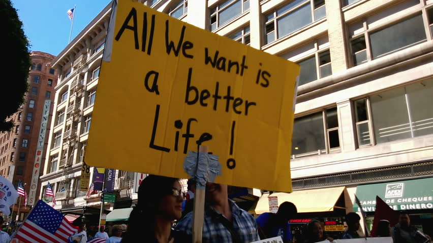 """A Better Life"" Rally Sign. A large yellow picket sign that reads, ""All We Want Is A Better Life!"" is held up during an immigration rally in downtown Los Angeles on September 22, 2013."