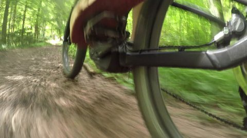 CLOSE UP: Extreme downhill biker riding e-bike along the singletrack trails and winding track in mountain bike park. Freeride biker riding electric bicycle on steep terrain through forest