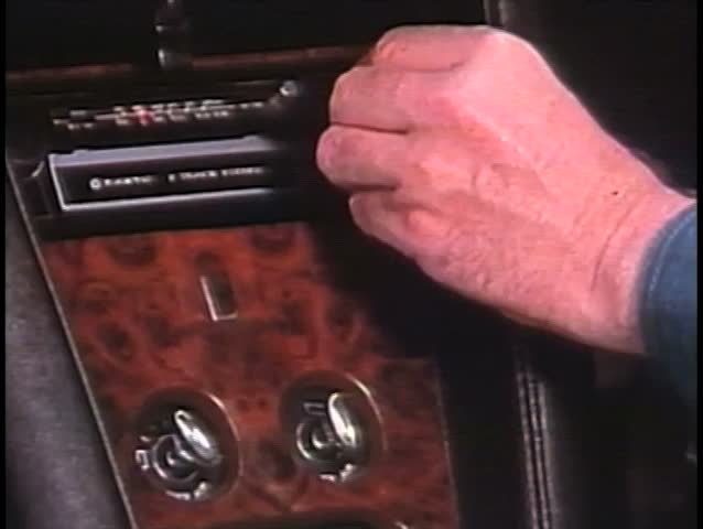 Close-up of hand changing channel on car radio
