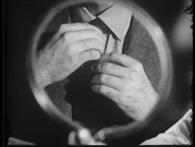 Close-up of man fixing tie in mirror