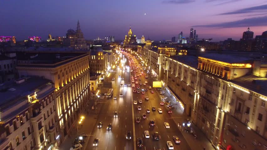 Sadovoe ring evening road traffic. Center of Moscow night illumination. Aerial drone from above view to moving cars. Stalin skyscrapers and modern business centers at background.