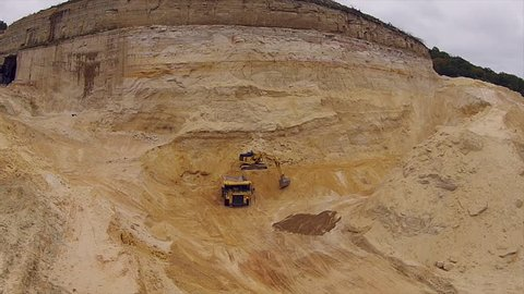 Heavy Equipment in an open pit mine, excavator loading a haul truck with quartz sand used for fracking