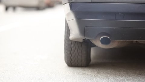 Close up view car exhaust pipe and wheel, vehicle move away with sound and smoke from tailpipe. Starting automobile from rear side, focus on discharge hole.