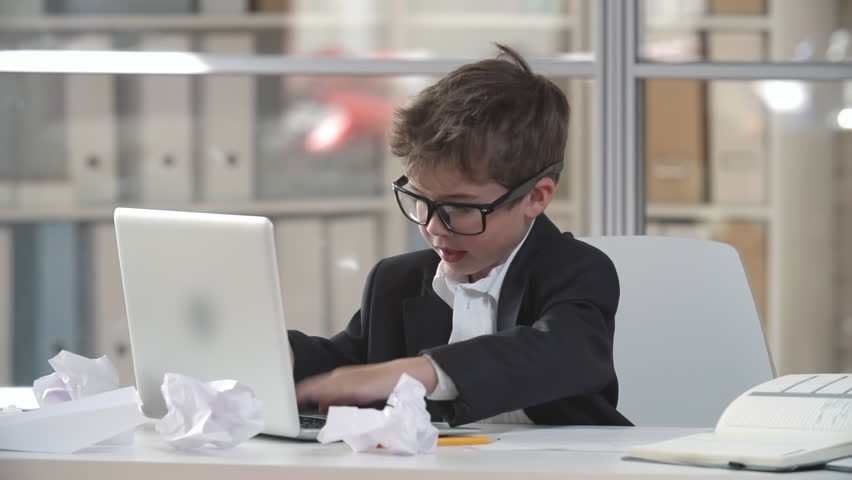 Tired little boy in business suit and glasses sitting at table typing on laptop. Then taking glasses off and blowing on them to clean.