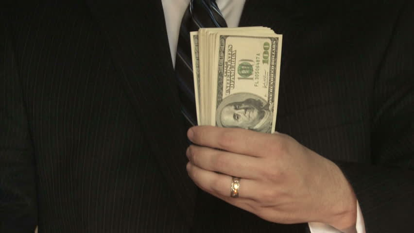 A businessman in a suit counts hundred dollar bills in front of him