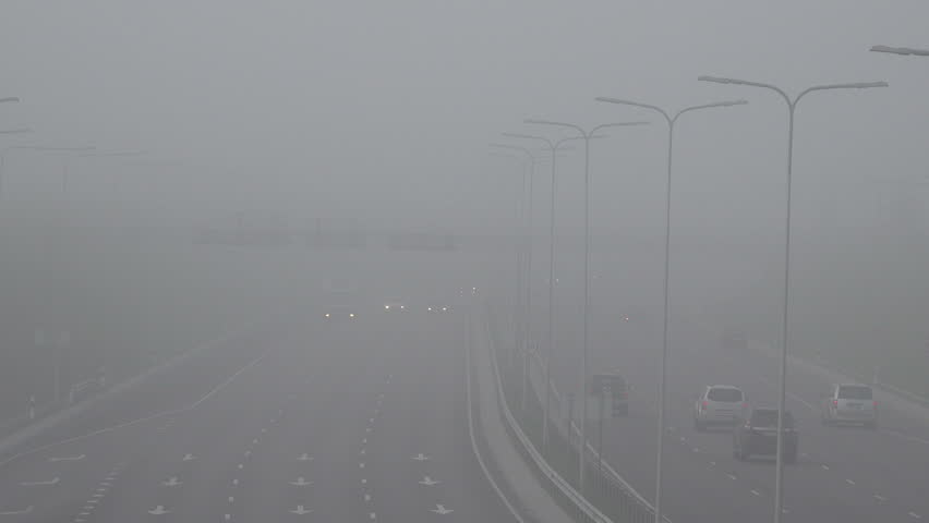 automobiles cars covered with heavy fog and haze. City face serious air pollution and poor air quality. Static shot.