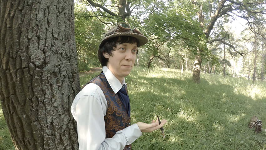 Young man in old-fashioned clothes smokes cigarette while standing near tree side view slow motion | Shutterstock HD Video #18698459