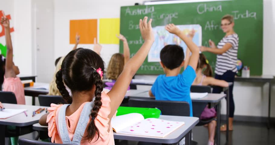 Smiling school kids raising hand in classroom at school 4k