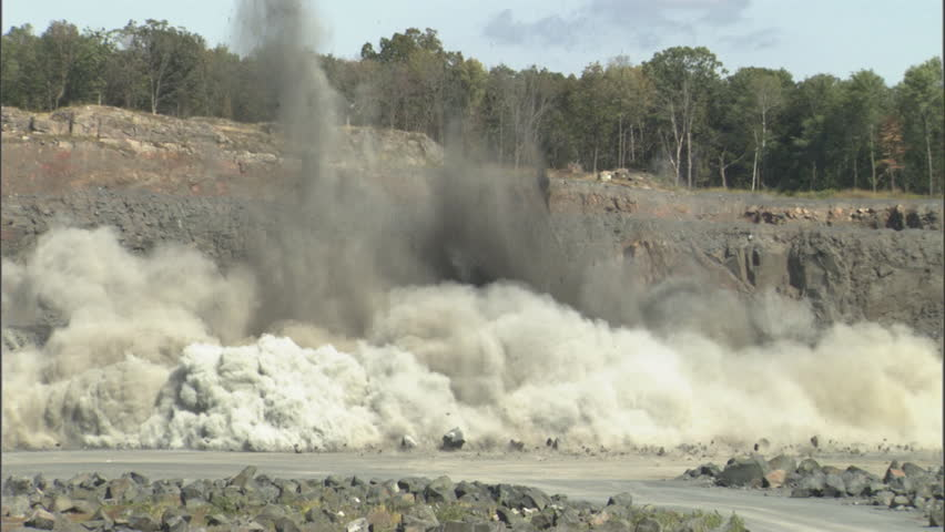 An explosion in a rock quarry send dust and debris into the air. This industrial strip mine site was conducting a controlled detonation of high explosives in order to create smaller chunks of rock.
