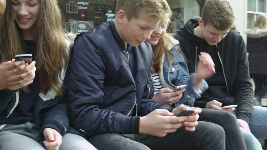 Teenage Friends In Town Using Mobile Phones Shot On R3D