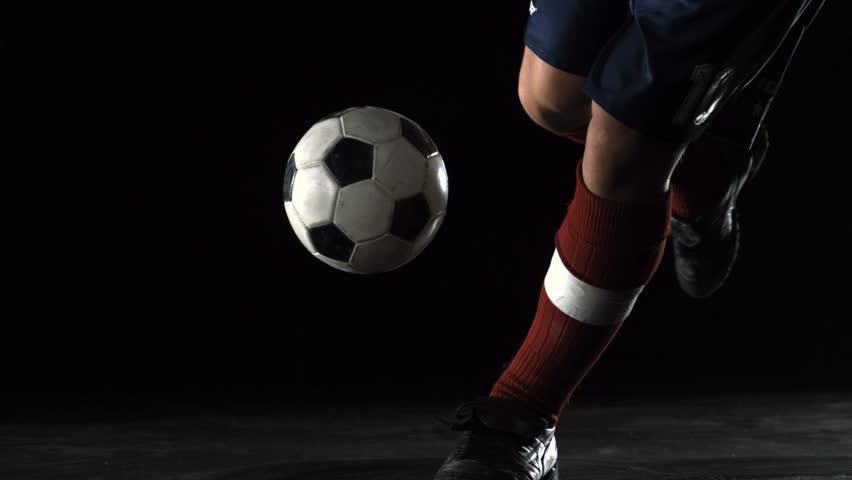 Close-up foot kicking soccer ball, Slow Motion
