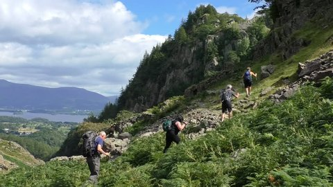 Group of four senior hikers with backpacks and walking trekking poles are climbing mountain slope in Lake District, UK.Beautiful scenery with Derwent Water in the background