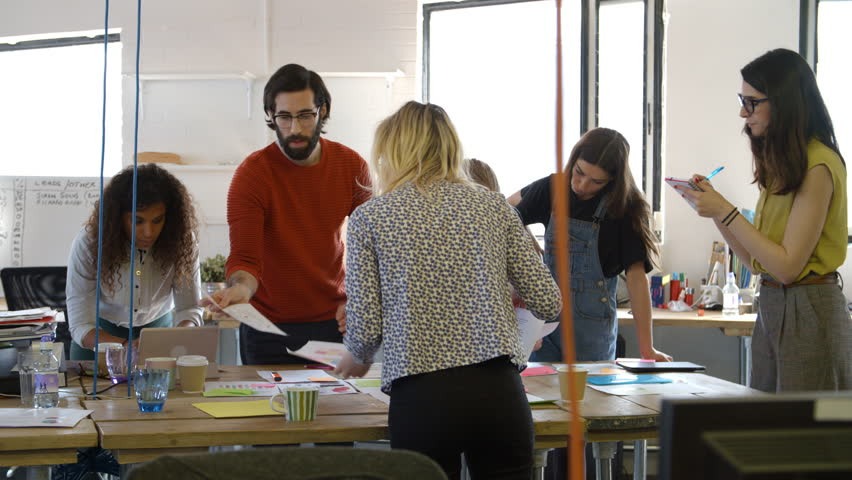 Group Of Designers Meeting Around Table In Modern Office   Shutterstock HD Video #18820097