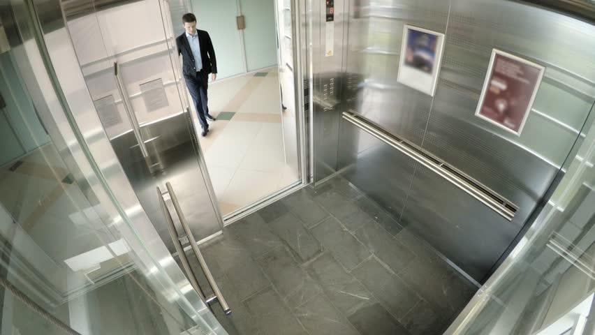 Businessmen riding in Elevator.